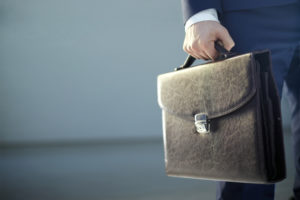 Photo of a man in a suit carrying a briefcase.