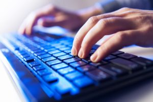 Photo of a man typing on a keyboard with blue backlighting.